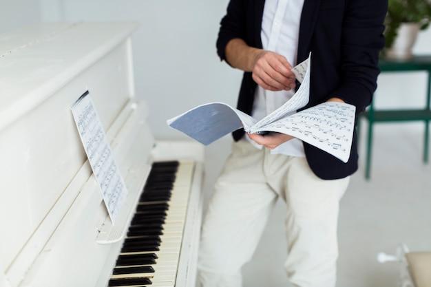 Sección media del hombre que pasa las páginas de las hojas musicales cerca del piano de cola.