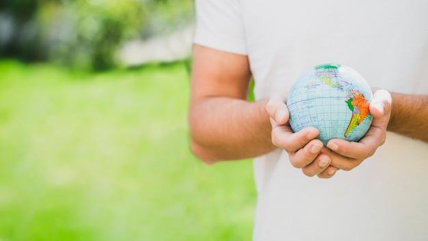 Sección media del hombre que sostiene el globo en la mano