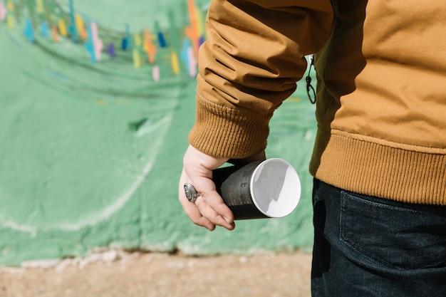 Sección media de un hombre que sostiene la lata de aerosol frente a la pared de graffiti