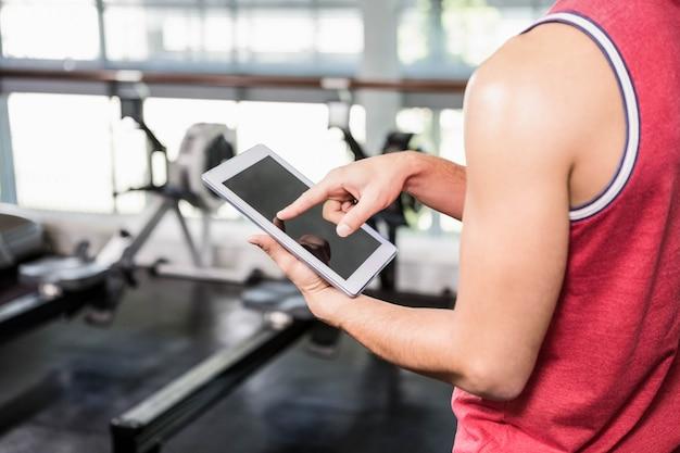 Sección media del hombre que usa la tableta en el gimnasio