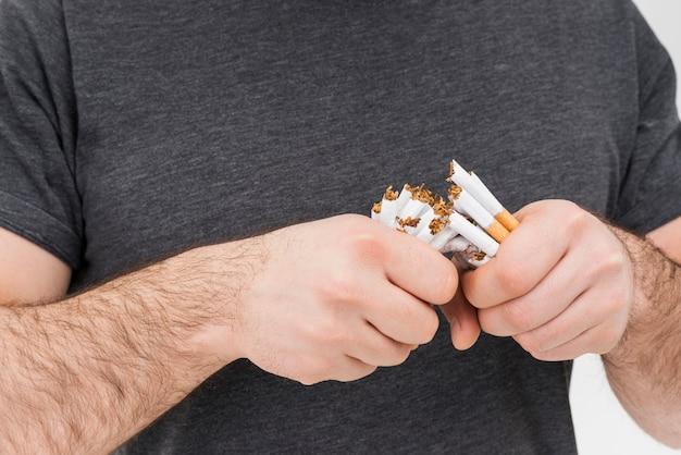 Sección media de un hombre rompiendo los cigarrillos con las manos