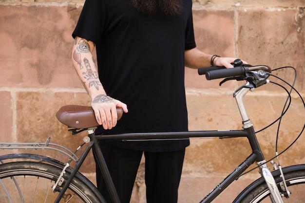 Sección media de un hombre en ropa negra de pie con su bicicleta