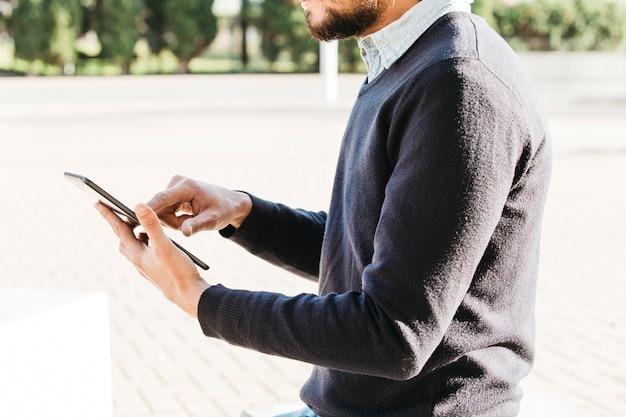 Sección media de un hombre sentado en el parque usando un teléfono móvil con pantalla táctil