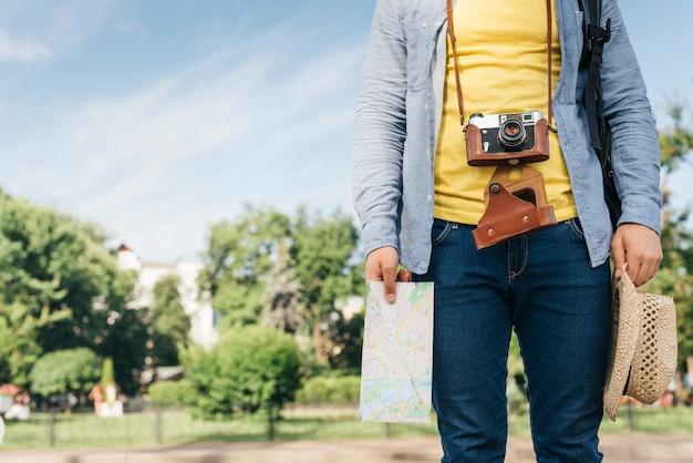 Sección media del hombre turista que lleva la cámara y que sostiene el mapa y el sombrero en el parque