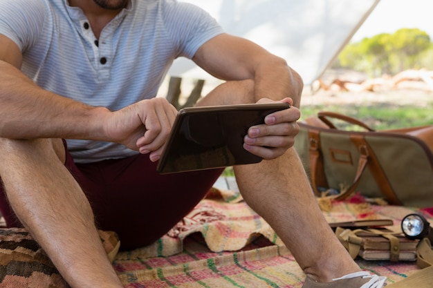 Sección media del hombre usando tableta en tienda