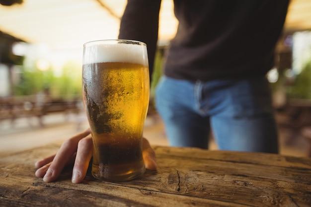 Sección media del hombre con vaso de cerveza