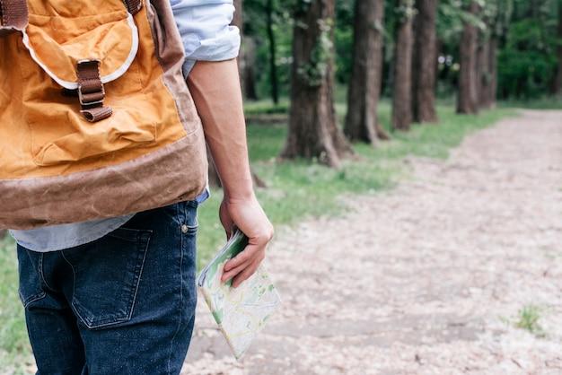 Sección media del hombre viajero que sostiene un mapa llevando mochila al aire libre