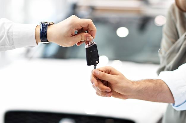 Sección media de la joven pareja comprando un coche nuevo en el showroom