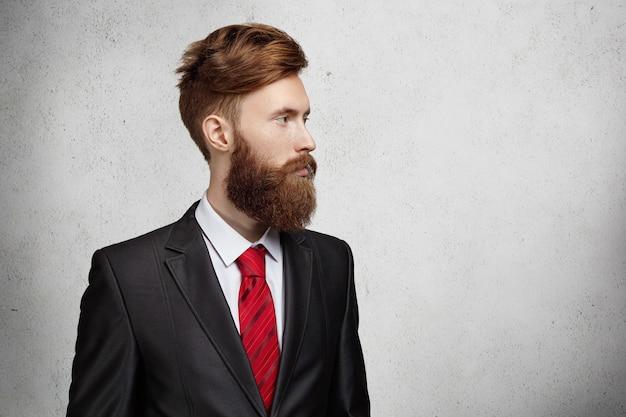 Sección media del joven trabajador de oficina caucásico guapo o autónomo con barba elegante y corte de pelo vestido con traje elegante mirando a la pared en blanco