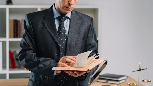 Sección media del libro de lectura maduro del abogado en la oficina