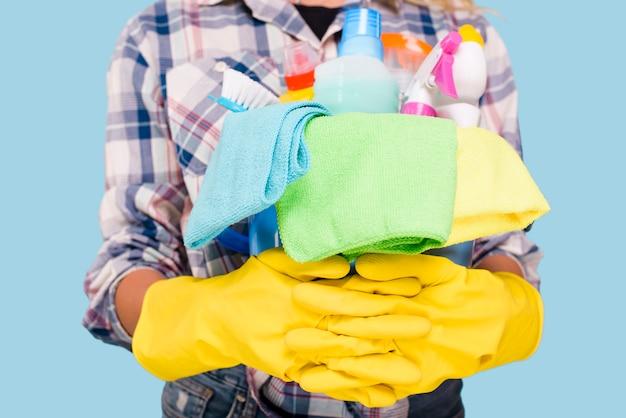 Sección media del limpiador que sostiene el balde con productos de limpieza con guantes amarillos
