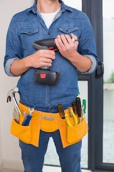 Sección media de un manitas con taladro y cinturón de herramientas