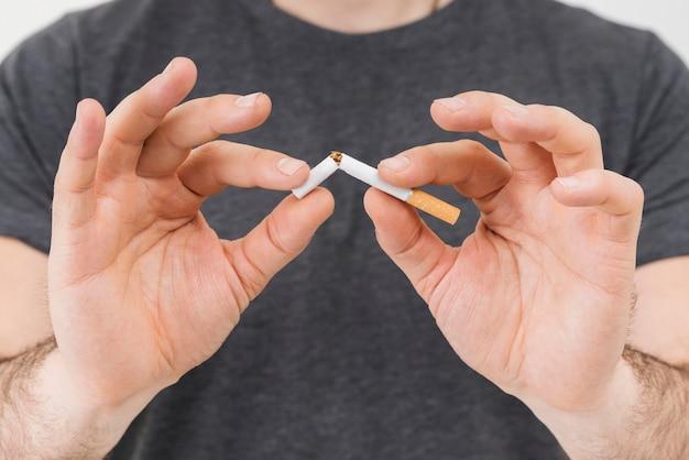 Sección media de la mano de un hombre rompiendo el cigarrillo