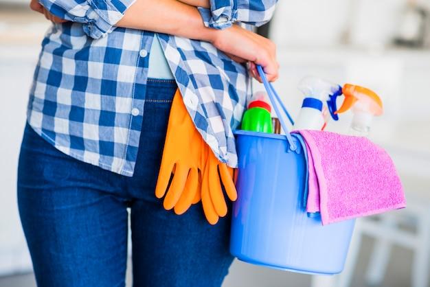 Sección media de la mano de la mujer con equipos de limpieza en el cubo.