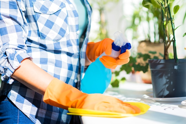 Sección media de la mano de la mujer que limpia la superficie blanca con un desinfectante en spray