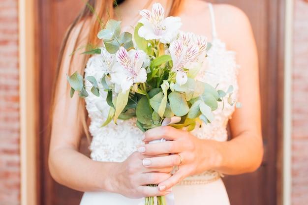 Sección media de las manos de una novia con un hermoso ramo de flores