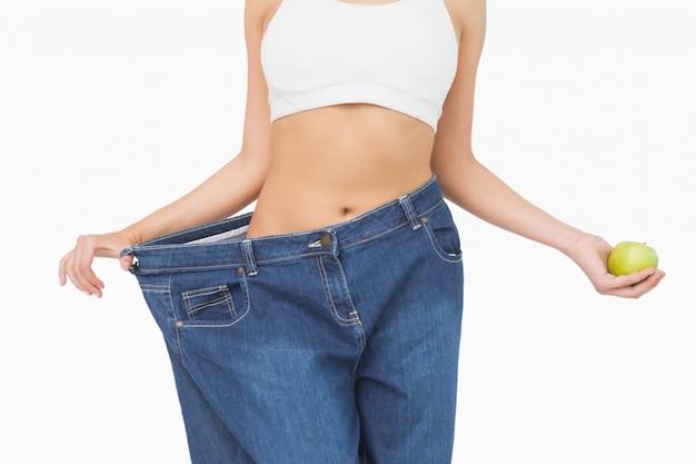 Sección media de mujer delgada con pantalones vaqueros demasiado grandes sosteniendo una manzana