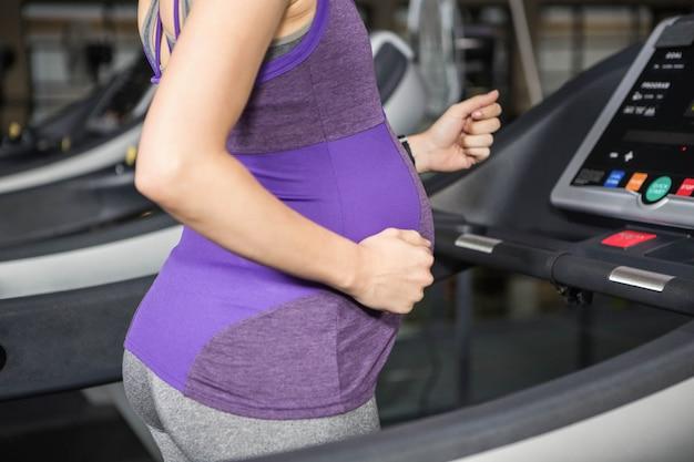 Sección media de mujer embarazada corriendo en la cinta en el gimnasio.