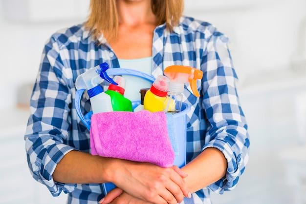 Sección media de la mujer con equipos de limpieza en el cubo azul