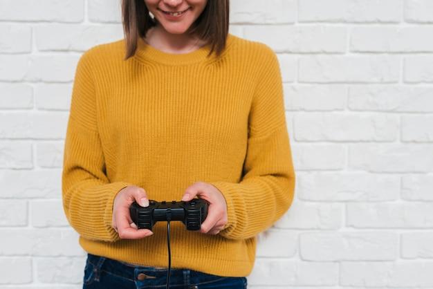 Sección media de una mujer joven jugando al videojuego con joystick