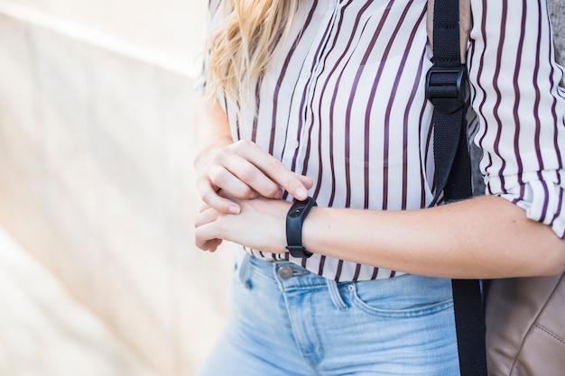 Sección media de la mujer joven que controla tiempo en el reloj digital