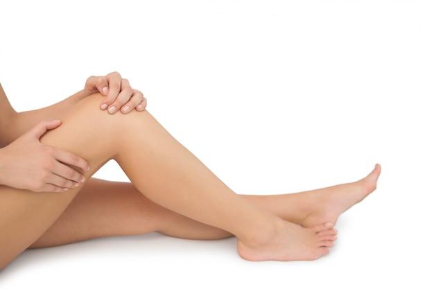 Sección media de la mujer joven que se sienta en el piso que toca su rodilla herida