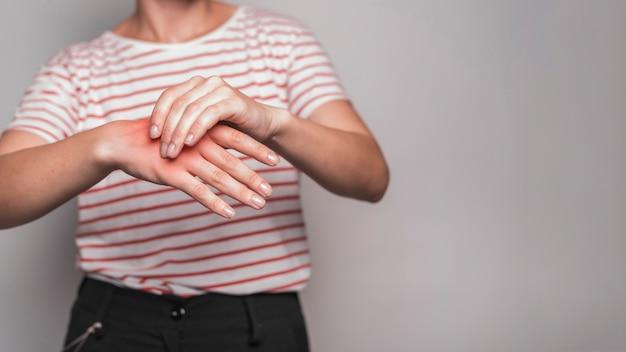 Sección media de la mujer joven que tiene dolor en la mano contra fondo gris
