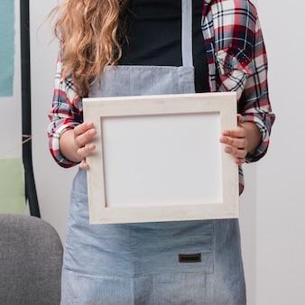 Sección media de la mujer con marco de fotos blanco