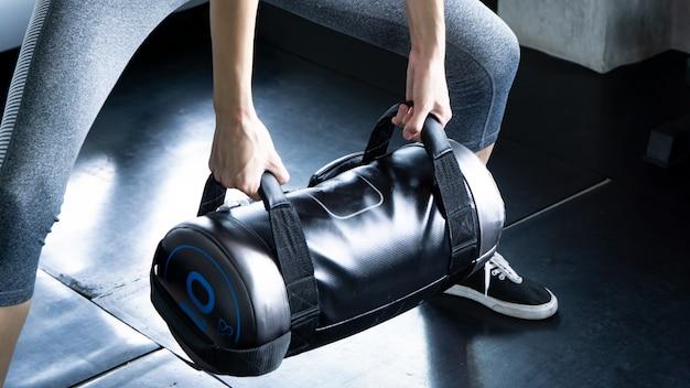 Sección media de mujer musculosa, levantamiento de pesas en el gimnasio