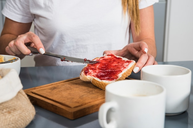 Sección media de una mujer que aplica mermelada roja en el pan con un cuchillo de mantequilla