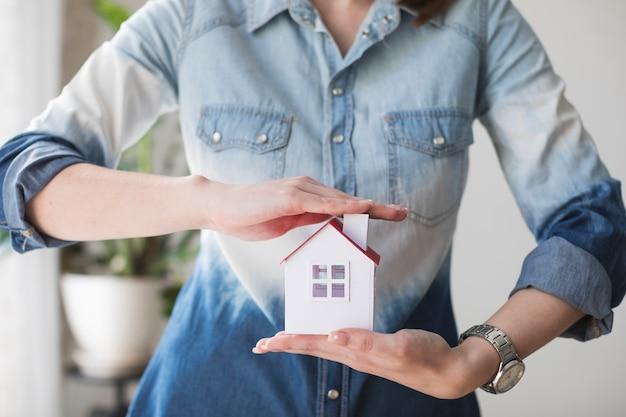 Sección media de la mujer que protege el modelo de casa en la oficina
