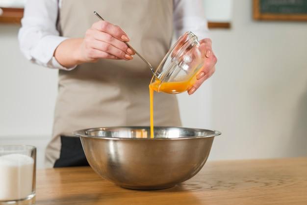 Sección media de la mujer que vierte la yema de huevo en el recipiente de acero inoxidable en la mesa de madera