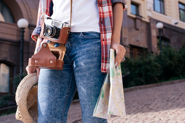 Sección media de una mujer sosteniendo un mapa y un sombrero con cámara mientras viaja solo