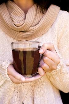Sección media de una mujer sosteniendo una taza transparente de té de hierbas