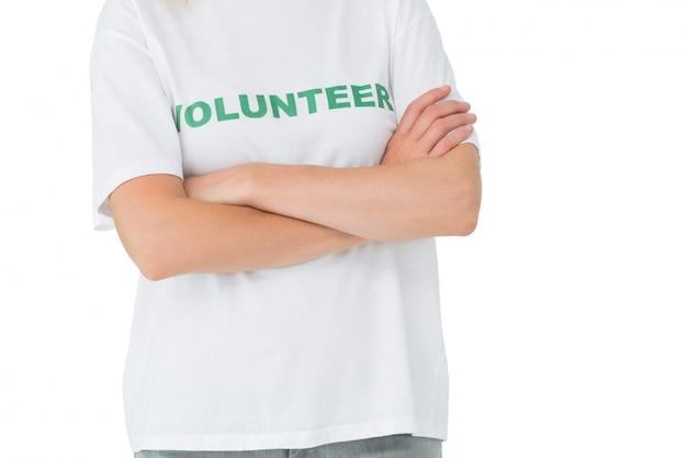 Sección media de una mujer voluntaria de pie con los brazos cruzados