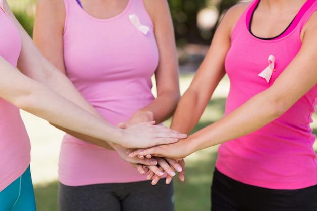 Sección media de mujeres voluntarias formando pila de manos