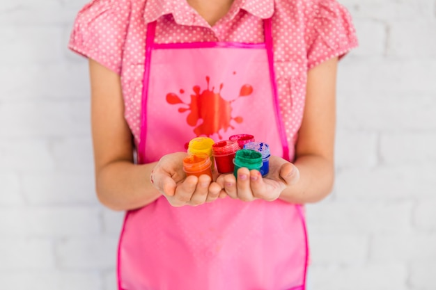 Sección media de una niña con botellas de pintura de colores en la mano