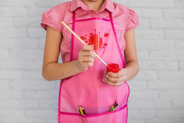 Sección media de una niña con pincel y pintura roja botella