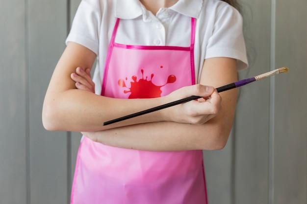 Sección media de una niña sosteniendo de pie con el brazo cruzado con pincel en la mano