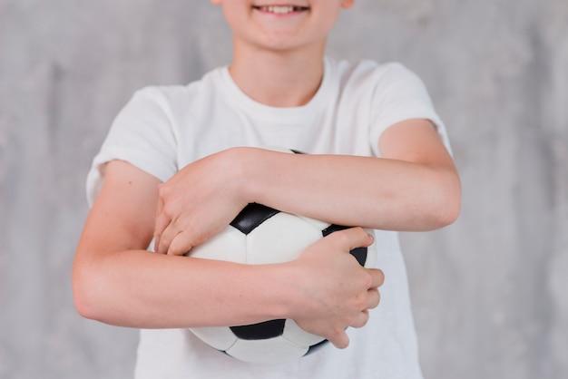 Sección media de un niño abrazando una pelota de fútbol contra una pelota de concreto