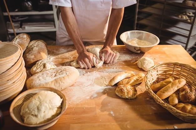 Sección media de panadero amasando una masa
