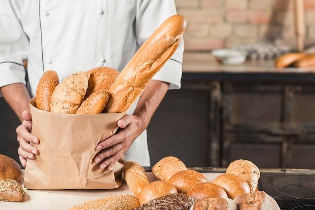 Sección media del panadero masculino con bolsa de papel con diferentes tipos de pan