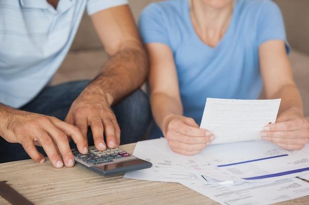 Sección media de una pareja con facturas y calculadora