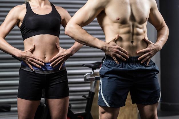 Sección media de la pareja en forma posando en el gimnasio crossfit