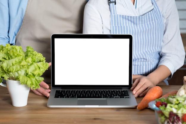 Sección media de una pareja de pie detrás del mostrador de la cocina con una pantalla blanca en blanco y verduras