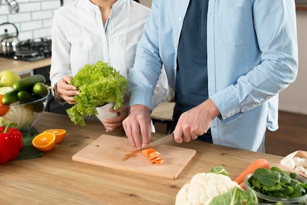 Sección media de pareja preparando la comida en el mostrador de la cocina