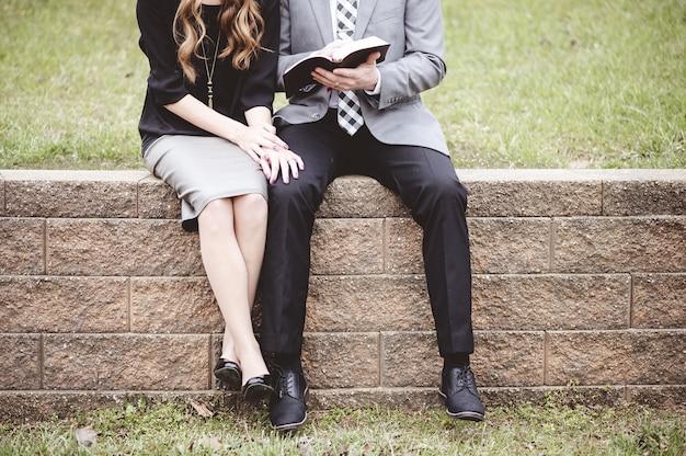 Sección media de una pareja sentada en bloques y leyendo un libro con amor