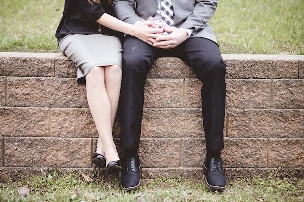 Sección media de una pareja sentada en bloques y orando juntos