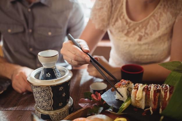 Sección media de pareja con sushi