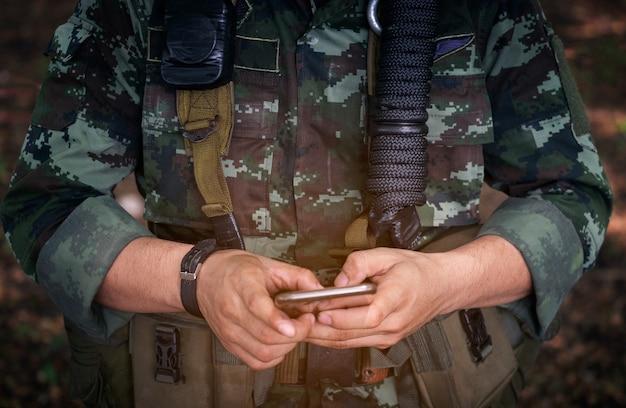 Sección media de un soldado militar usando un teléfono móvil en la guerra del campo de entrenamiento.